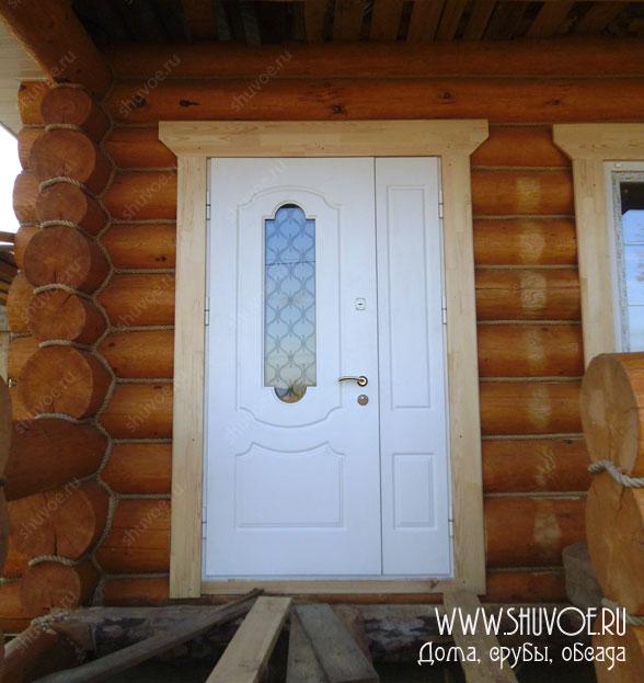 Металлическая входная дверь в деревянном доме. Установлена в окосячку, с наличниками.