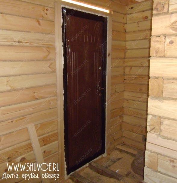Фото установки обсады и входной двери в брусовом доме