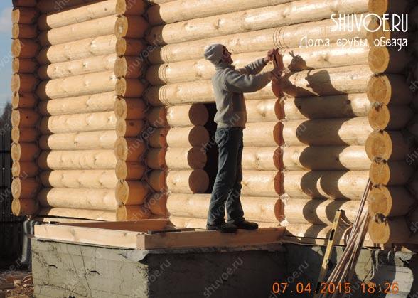 Плотник выбирает паз под брусовой прируб.