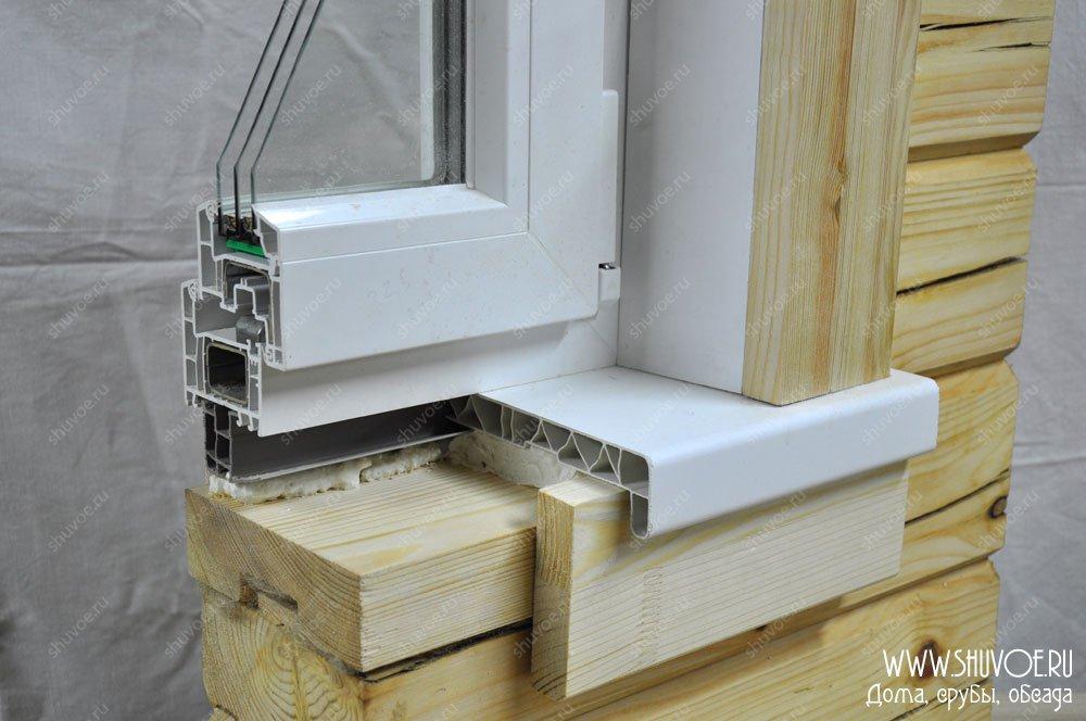 Брусовый дом с белым пластиковым окном и деревянными...